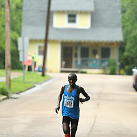 The lead runner makes his turn off of Clayton Ave onto Woodlawn Street as he pulls away from the other runners.