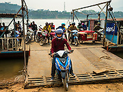 11 MARCH 2016 - LUANG PRABANG, LAOS: A motorcycle gets off a ferry across the Mekong River near Luang Prabang. Laos is one of the poorest countries in Southeast Asia. Tourism and hydroelectric dams along the rivers that run through the country are driving the legal economy.       PHOTO BY JACK KURTZ