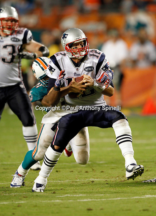 New England Patriots quarterback Tom Brady (12) gets sacked by Miami Dolphins linebacker Cameron Wake (91) in the second quarter of the NFL week 1 football game against the Miami Dolphins on Monday, September 12, 2011 in Miami Gardens, Florida. The Patriots won the game 38-24. ©Paul Anthony Spinelli
