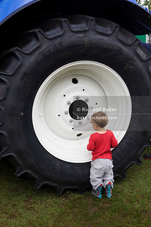 A small boy shows a fascination for a huge tractor wheel at the Lambeth country fair in inner-city south London. Possibly never having seen a large machine such as this at close-quarters, the lad stares at the giant nuts that attach the wheel to the main frame. Perhaps he is captivated by its immensity and scale, so much larger than his toy vehicle at home in his toy box.