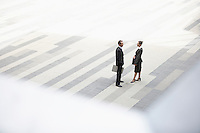 Businessman and businesswoman standing and talking in outdoor plaza elevated view
