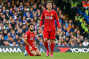 Liverpool forward Roberto Firmino (9) walks away from Liverpool forward Mohamed Salah (11) on his knees during the Premier League match between Chelsea and Liverpool at Stamford Bridge, London, England on 22 September 2019.