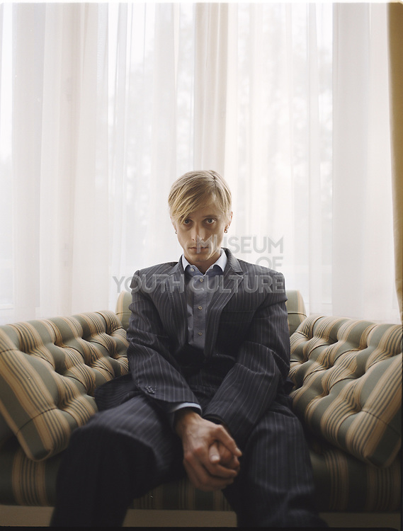 Young man sitting in bay window looking very serious.