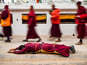 16 MARCH 2017 - KATHMANDU, NEPAL: A Buddhist monk prostrates himself while making a pilgrimage at Boudhanath Stupa in Kathmandu. The stupa is the holiest site in Nepali Buddhism. It is also the center of the Tibetan exile community in Kathmandu. The Stupa was badly damaged in the 2015 earthquake but was one of the first buildings renovated.      PHOTO BY JACK KURTZ