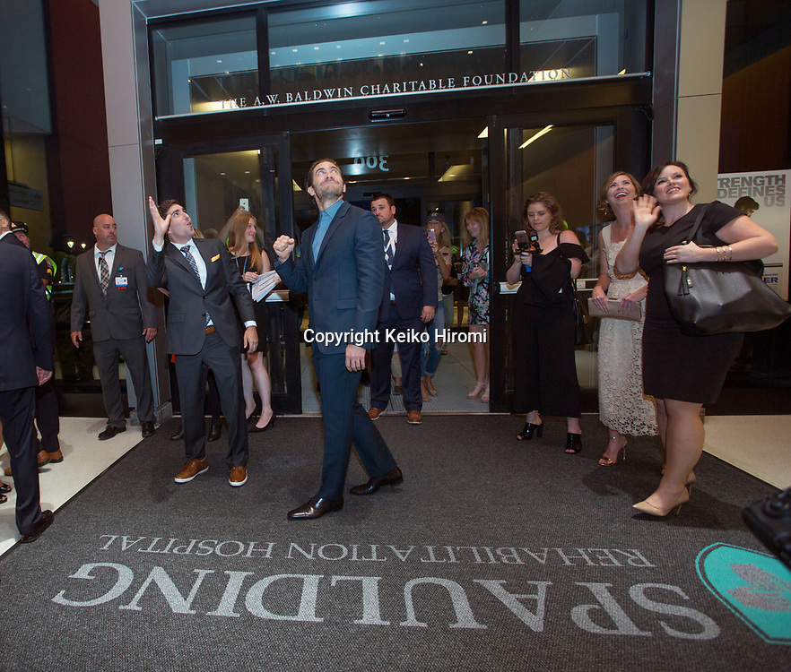 """September 12, 2017, Spaulding Rehabilitation Hospital, Charlestown, Massachusetts, USA: Actor Jake Gyllenhaal (center) and Boston Marathon bombing survivor Jeff Bauman (L) looking up to the patients who gather on balcony of front lobby at Spaulding Rehabilitatiion Hospital at the U.S. premiere of the movie """"Stronger"""" at the Spaulding Rehabilitation Hospital in Boston.  Gyllenhaal plays Bauman in the film."""