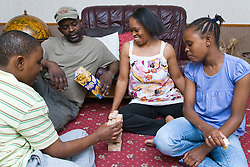 Family playing a game of Jenga together at home,