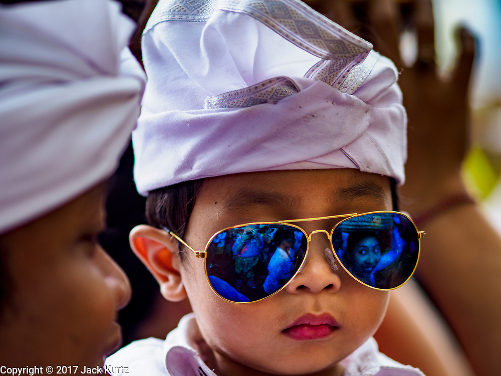 """02 AUGUST 2017 - UBUD, BALI, INDONESIA: A boy in his father's arms waits to get into the temple during the """"Merchants' Day"""" ceremony at the Pura (Temple) Melanting Pasar Ubud, the small Hindu temple in the Ubud market. It's a day that merchants throughout Ubud come to the temple to make offerings and pray for prosperity.    PHOTO BY JACK KURTZ"""