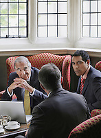 Three business men talking over laptop in lobby