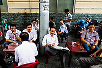 Vietnamese men drink coffee and tea on the streets of downtown Ho Chi Minh City, Vietnam.