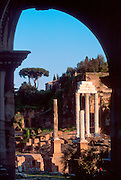 ITALY, ROME, ROMAN FORUM view through Arch of Tiberius to the three columns of the Temple of Castor and Pollox and Palantine Hill