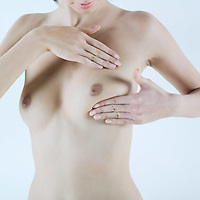 studio shot picture of a young beautiful breast naked  woman doing breast palpation