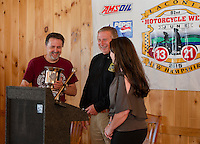 Mayor Ed Engler is presented with the Fritzie Baer Award by Charlie St Clair and Jennifer Anderson during the Motorcycle Week kickoff event held at Faro Restaurant in Weirs Beach Thursday morning.  (Karen Bobotas/for the Laconia Daily Sun)