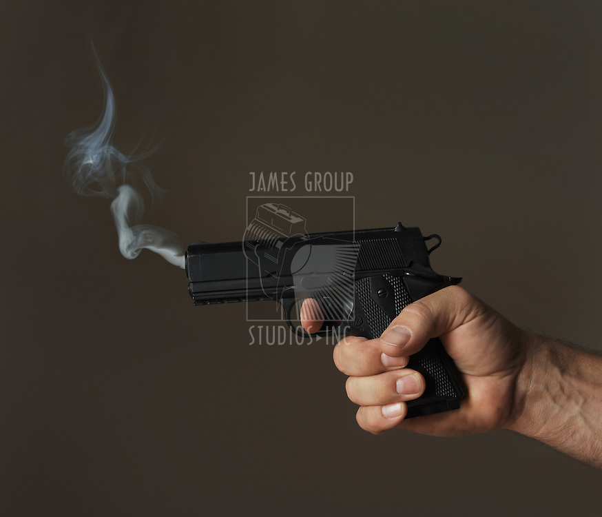 hand holding smoking pistol on dark background