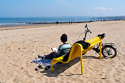 Portobello, Scotland, UK. 25 April 2020. Views of people outdoors on Saturday afternoon on the beach and promenade at Portobello, Edinburgh. Good weather has brought more people outdoors walking and cycling. Police are patrolling in vehicles but not stopping because most people seem to be observing social distancing. Woman relaxing on beach by reading a book  book. Iain Masterton/Alamy Live News