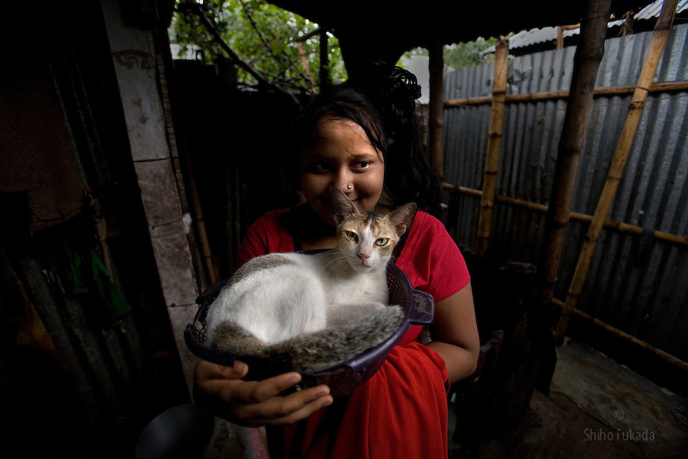 Sex worker Munnie, 15, carries her pet cat at brothel in Tangail, Bangladesh.