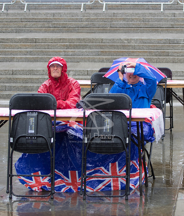 Trafalgar Square, London, June 12th 2016. Rain greets Londoners and visitors to the capital's Trafalgar Square as the Mayor hosts a Patron's Lunch in celebration of The Queen's 90th birthday. PICTURED: Undeterred and full of British spirit a couple refuse to let the rain dampen their day.