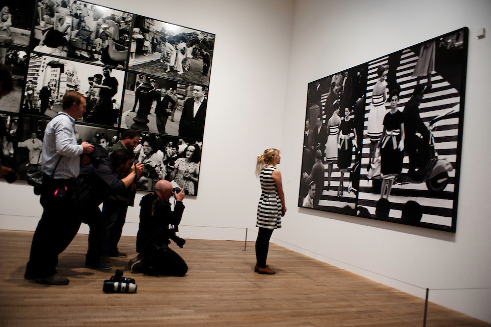 London, UK - 8 October 2012: photographers take pictures at a member of the staff posing in front of 'Piazza di Spagna, Rome 1960' by William Klein. The exhibition examine the relationship between the work of William Klein (b.1928) and that of Daido Moriyama (b.1938). Taking as its central theme the cities of New York and Tokyo, the show explores both artists' celebrated depictions of modern urban life.