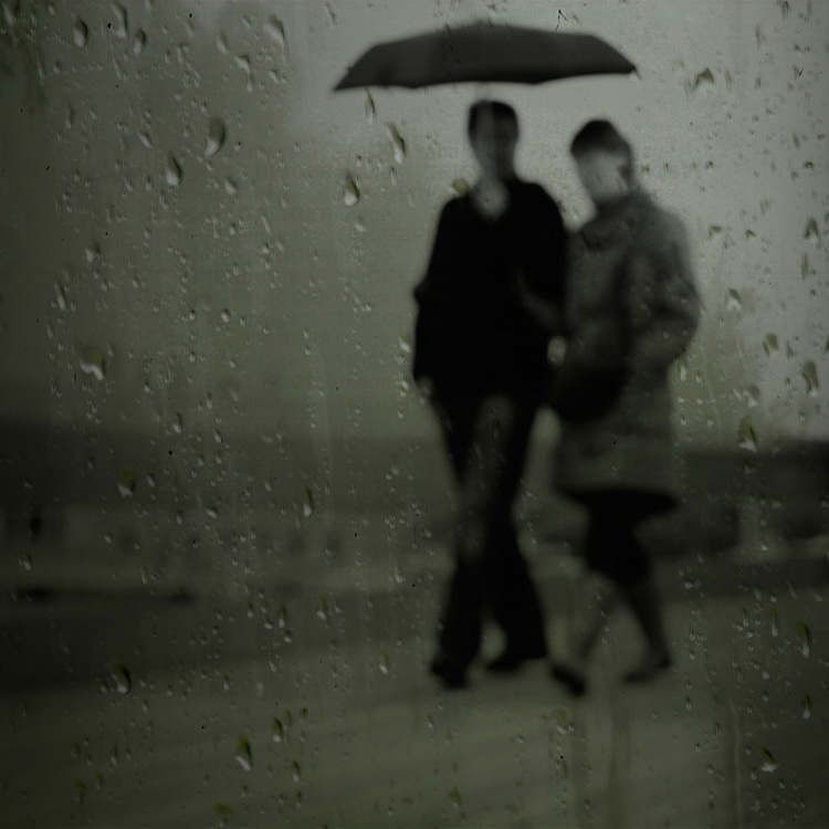Two young people walking in the rain holding an umbrella