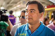 16 FEBRUARY 2013 - BANGKOK, THAILAND:  ABHISIT VEJJAJIVA, former Prime Minister of Thailand, walks into the MoChit BTS station to campaign for his party colleague Sukhumbhand Paribatra ahead of Bangkok's governor election. Bangkok residents go to the polls on March 3 to elect a new governor. Sukhumbhand Paribatra, the current governor, is running on the Democrat's ticket and is getting help from national politicians like Abhisit Vejjajiva, the former Thai Prime Minister. One of Sukhumbhand's campaign pledges is to improve Bangkok's mass transit and transportation system. Abhisist road the BTS Skytrain to campaign for Sukhumbhand.     PHOTO BY JACK KURTZ