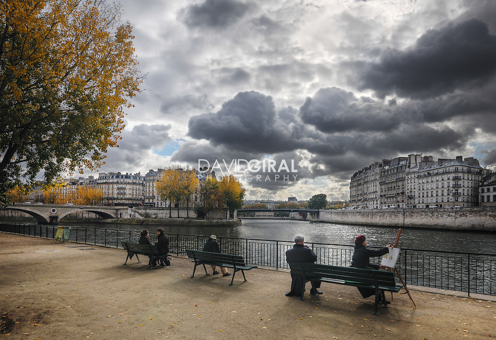 people sitting and painting on the Seine quays on a beautiful cloudy afternoon