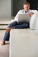 Young man sitting on sofa using laptop portrait