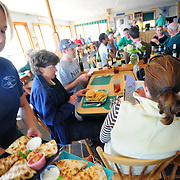 "9/7/09 - HARPSWELL, Maine -- Dolphin Marina Waitress Kristy Brown serves a family an order of Quesadillas at the Restaurant on Monday at lunch time. New co-owners, Chris and Billy Saxton plan on making changes to the family-run property in the coming months. They will increase the size of the restaurant, adding tables -- but keeping the ""charm"" of the location. They also plan on increasing to over 100 moorings in the bay. Photo by Roger S. Duncan"