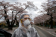 "A woman, who went by the name of Miki, walks along a street famed for having one of Japan's longest cherry blossom ""tunnels"" in Tomioka, Fukushima Prefecture, Japan on Wednesday 20 April  2011. The woman, a former nuclear power plant employee, was visiting the town -- which falls inside the now legally enforced evacuation zone -- to see the famed cherry trees and pick up some belongings from her home..Photographer: Robert Gilhooly"