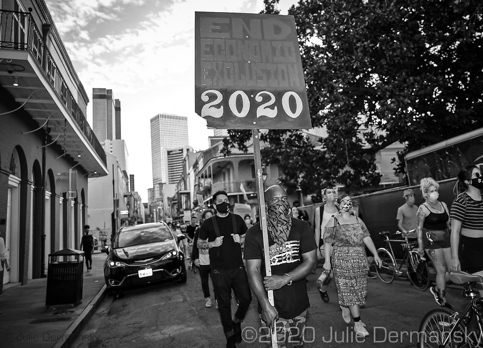 A man holding a proteset sign at a Take 'Em Down NOLA  rally and march held on June 27, 2020 . The organizers warned the city it had three days left to take down white supremacist monuments now being referred to as monuments to white mediocrity,  or else the monuments will come down by unauthorized means- A few hundred people came out to protest against police violence and racial inequality and marched through the French Quarter stopping at monuments on the groups list that it demands be taken down. The organizers explained the historical significance of each statue.
