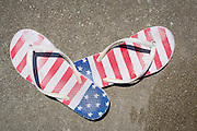 A pair of American flag sandals sit on the pool deck as Revelers swim during the Independence Day Pool Party at the Milpitas Sports Center in Milpitas, California, on July 4, 2015. (Stan Olszewski/SOSKIphoto)