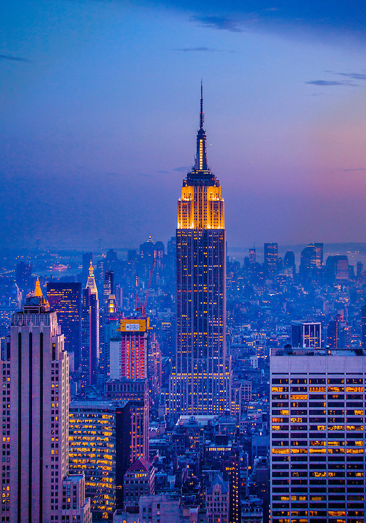 A deep blue and magenta, New York skyline at dusk, seen from the Top of the Rock observation deck in Rockefeller Center's RCA (now Comcast) Building, aka 30 Rock, looking south to Midtown, the Empire State Building and Lower Manhattan