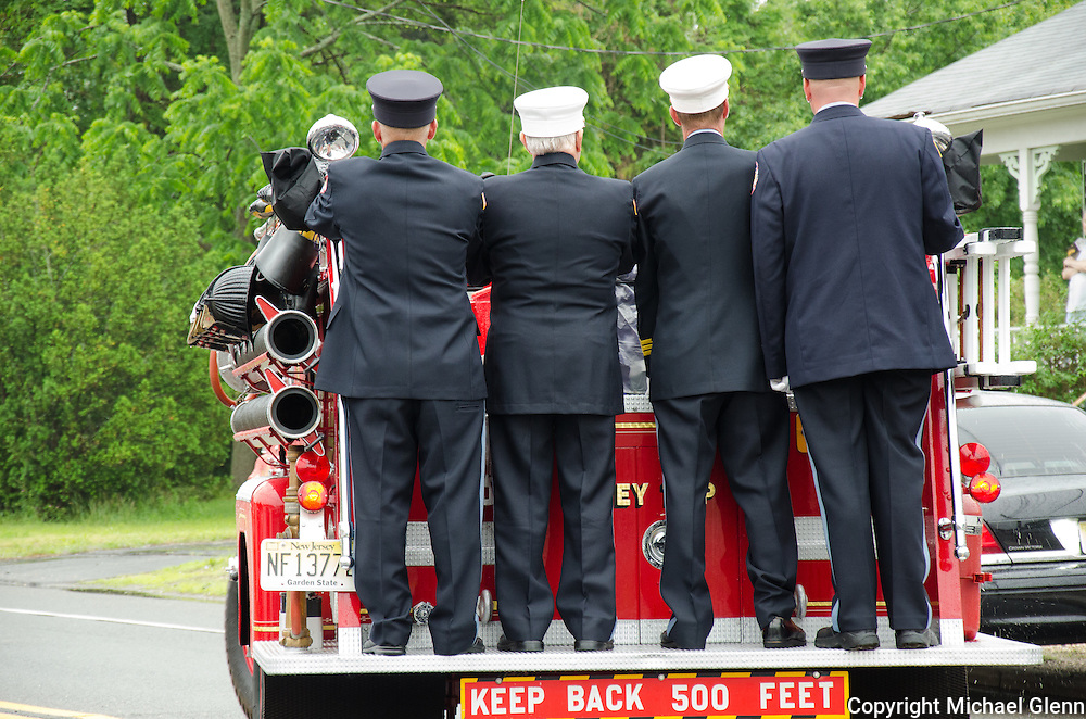 10Jun2013/Lanoka Harbor/NJ/USA/Funeral Service for LHFD Chief Kevin Perrone who died suddenly after a battle with Kidney failure.  Firemen ride the back of the truck as the casket is brought to Good Luck cemetary