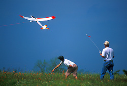 Stock photo of a man and boy flying a radio controlled airplane in a field