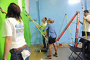 Restoration expert Nicole Curtis, center right, and Mike Verne, center left, of Bernzomatic, paint walls at Staten Island MakerSpace in New York,  Thursday, Oct. 22, 2015, to launch the Bernzomatic Find Your Fire Community Grants program.  MakerSpace is a community center still feeling the effects of Hurricane Sandy three years later.  Bernzomatic, the industry leader in handheld torches, is encouraging people to submit a community project for a chance to win one of three $10,000 grants and a visit from Curtis. Go to Bernzomatic.com/Grants for more information.  (Photo by Diane Bondareff/Invision for Bernzomatic/AP Images)