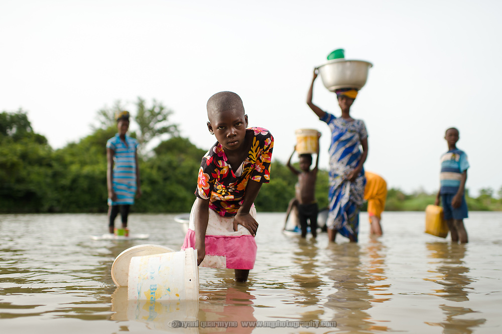 Thoiba collecting water for household use from the river about a kilometre's walk from her home in the Upper West Region of Ghana on 27 May 2014. She has to collect water each morning before school, and says she is sometimes late as a result.