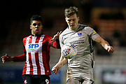 Sean Raggett of Portsmouth  and Tyreece John-Jules of Lincoln City  contest a loose ball during the EFL Sky Bet League 1 match between Lincoln City and Portsmouth at Sincil Bank, Lincoln, United Kingdom on 28 January 2020.