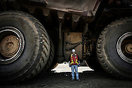 An Albian Sands official stands dwarfed by a giant mining truck Caterpillar CAT 797B operating with Shell Albian Sands oil field, in Fort Mc Murray, Alberta. The CAT 797B can carry a 400 tons load of tar sands. It's total gross weight of 590,000kg then exceed the Airbus A-380's 560 tons maximum take off weight. Michelin provide 55/80R63 XDR radial tires for giant mining truck Caterpillar CAT 797B. Size and capacity of giant mining trucks depend on progress by tyre manufacturer. Each tire weight 5,3 tons, has a 4 meter diameter and cost over 40,000$. 25 June 2008.