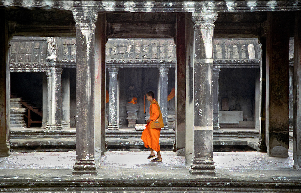 Buddhist monk walks across the main sanctuary at Angkor Wat, the main temple of the ancient city of Angkor, near Siem Reap. Cambodia, 2003.