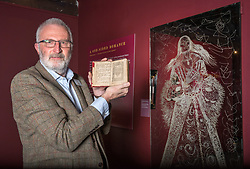 © Licensed to London News Pictures. 16/04/2018. Winchcombe, Gloucestershire, UK. Sudeley Castle's 'Royal Sudeley 1,000, Trials, Triumphs and Treasures'. Picture of DEREK MADDOCK, Sudeley Castle Archivist, holding a book with wife of Henry VIII Katherine Parr's formal signature beside life-size glass-engraved portrait of Katherine Parr by critically acclaimed artist, John Hutton. Treasures from Sudeley Castle's 1,000 year history have gone on show in a new exhibition. Called 'Royal Sudeley 1,000, Trials, Triumphs and Treasures', the newly refurbished exhibition includes a collection of priceless objects and curiosities. The exhibition includes a one-of-a-kind, life-size glass-engraved portrait of Katherine Parr by critically acclaimed artist, John Hutton. The artwork was re-discovered during the refurbishment of a holiday cottage on the estate, where it had been for decades. Its importance has now been realised and so it has been brought into the exhibition collection. Numerous items of historic significance are also on display, such as a lock of Katherine Parr's hair, her prayer book and an intricate lace christening canopy believed to have been worked on by Anne Boleyn for the christening of her daughter, Elizabeth I. Sudeley was a royal residence, closely associated with some of the most famous English monarchs, including Edward IV, Richard III, Henry VIII, Lady Jane Grey, Katherine Parr, Elizabeth I and Charles I. The Castle was even home to a secret Queen of England, Eleanor Boteler, whose royal status was unknown for centuries. Photo credit: Simon Chapman/LNP