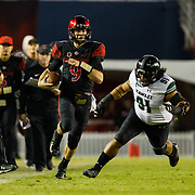 24 November 2018: San Diego State Aztecs quarterback Ryan Agnew (9) beats Hawaii Warriors defensive lineman Samiuela Akoteu (91) down the sideline for a first down late in the fourth quarter. The Aztecs closed out the season with a 31-30 overtime loss to Hawaii at SDCCU Stadium.
