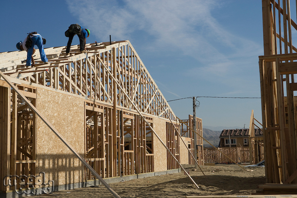 Two construction workers working on roof of half constructed house