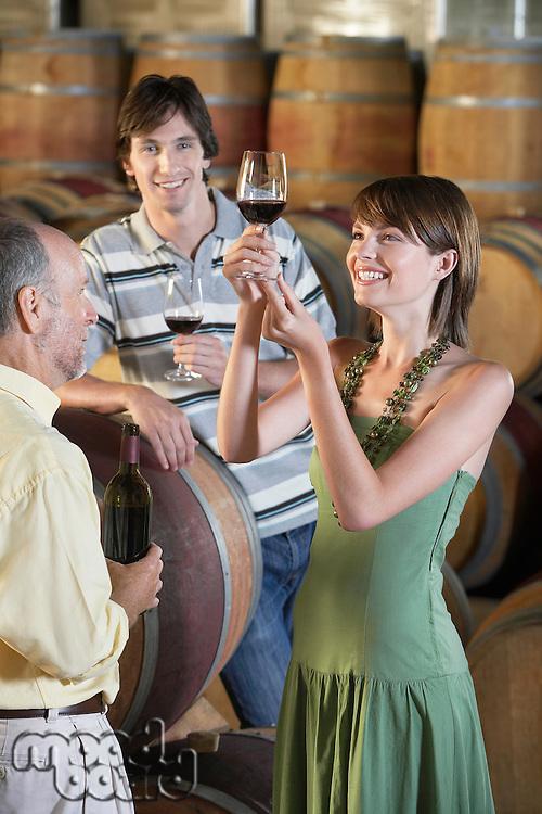 Three people wine-tasting beside wine casks