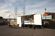HGV driver grabs early evening fast-food dinner from a mobile burger bar trailer in an overnight lorry park on the A126 in Grays