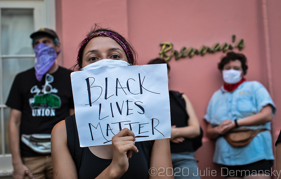A woman with a Black Lives Matter sign at a Take 'Em Down NOLA  rally and march held on June 27, 2020 . The organizers warned the city it had three days left to take down white supremacist monuments now being referred to as monuments to white mediocrity,  or else the monuments will come down by unauthorized means- A few hundred people came out to protest against police violence and racial inequality and marched through the French Quarter stopping at monuments on the groups list that it demands be taken down. The organizers explained the historical significance of each statue.