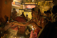 A woman gives an offering at a shrine near the Ganges River in Varanasi, India