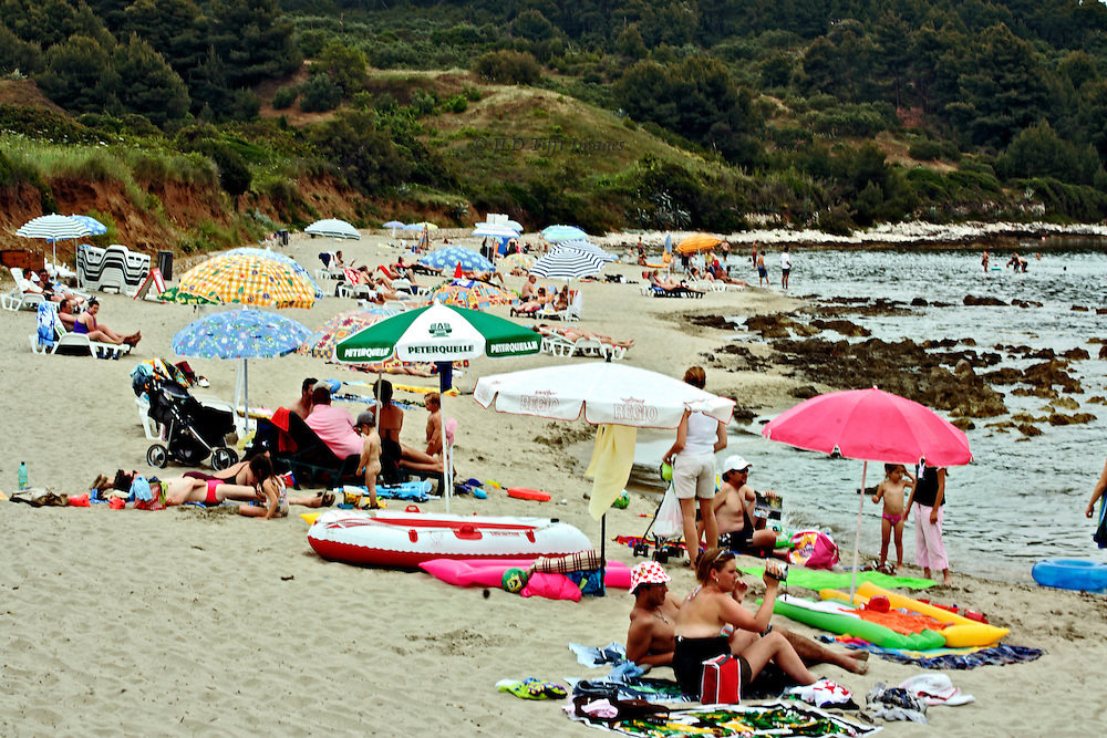Holidaymakers sunbathe with umbrellas, blowup toys, and blankets, on the beach in Korcula, Croatia.