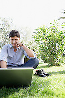 Businessman Using Laptop in Park