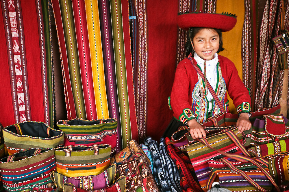 A young storekeeper minding a stock of woven textile in Chinchero, Peru.
