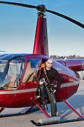 Evan Joseph with helicopter, prior to an aerial photo flight