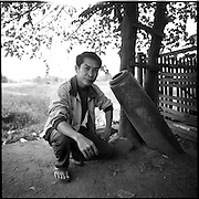 Voladet Phrasisombath, an instructor with UXO Lao,  poses next to an unexploded bomb outside his office in Xepon, Laos.