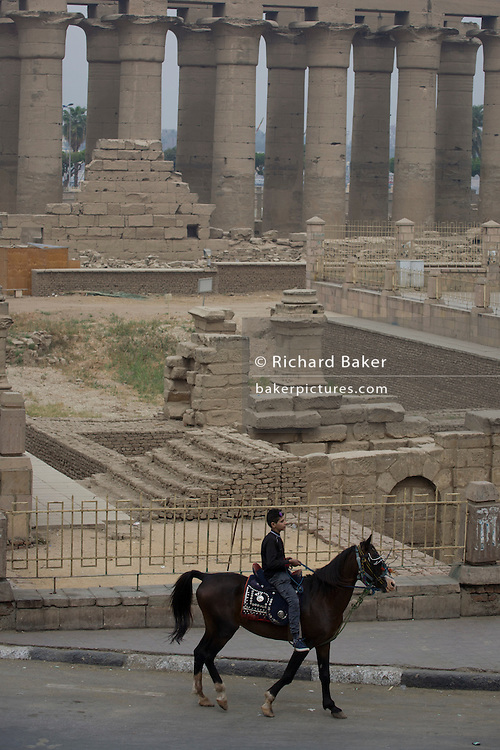 A young Egyptian man on a horse passes in front of the ancient Egyptian columns of Luxor Temple, Luxor, Nile Valley, Egypt. The temple behind was built by Amenhotep III, completed by Tutankhamun then added to by Rameses II. Towards the rear is a granite shrine dedicated to Alexander the Great and in another part, was a Roman encampment. The temple has been in almost continuous use as a place of worship right up to the present day.